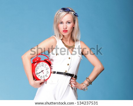 Portrait of pretty young woman in white dress against blue background timer red clock. Time management concept