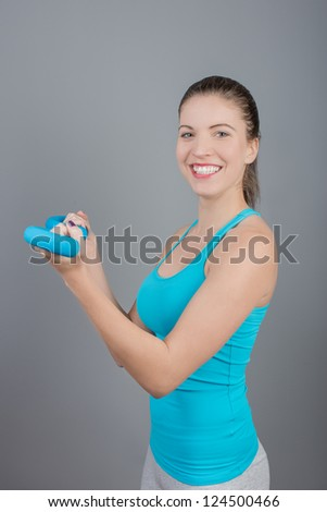 Portrait of pretty young woman lifting dumbbells during exercising