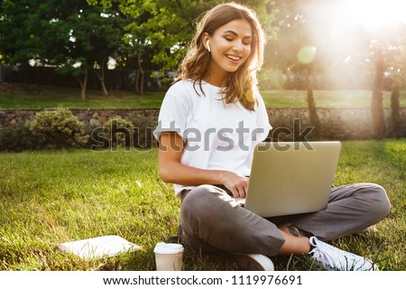 Portrait of pretty young woman sitting on green grass in park with legs crossed during summer day while using laptop and wireless earphone for video call