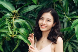 Portrait of pretty young woman standing near leaves outdoors