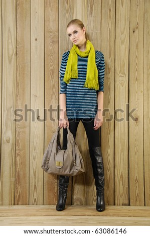 Portrait of pretty young Woman Wearing scarf holding handbag , natural wooden background