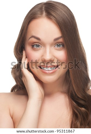 Portrait of pretty young woman with beautiful fresh make-up touching her face and looking surprised