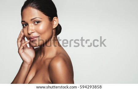 Portrait of pretty young woman with healthy skin posing against grey background. Natural beauty with clean and clear skin.