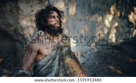 Portrait of Primeval Caveman Wearing Animal Skin Looks Around Forest Defending His Cave and Territory in the Prehistoric Times. Prehistoric Neanderthal or Homo Sapiens Leader