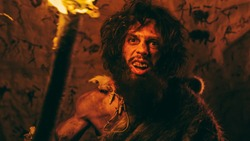 Portrait of Primeval Caveman Wearing Animal Skin Standing in His Cave At Night, Holding Torch with Fire and Attacking. Primitive Neanderthal Hunter / Homo Sapiens Screaming and Threatening