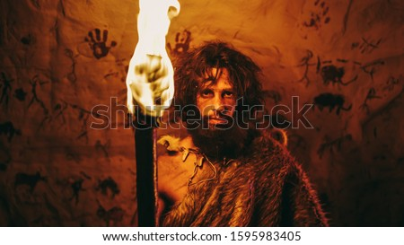Portrait of Primeval Caveman Wearing Animal Skin Standing in His Cave At Night, Holding Torch with Fire. Primitive Neanderthal Hunter / Homo Sapiens At Night Alone. In the Background Cave Art Drawings Stockfoto ©