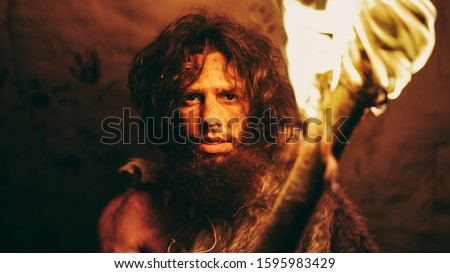 Portrait of Primeval Caveman Wearing Animal Skin Standing in His Cave At Night, Holding Torch with Fire. Primitive Neanderthal Hunter / Homo Sapiens At Night Alone in His Den