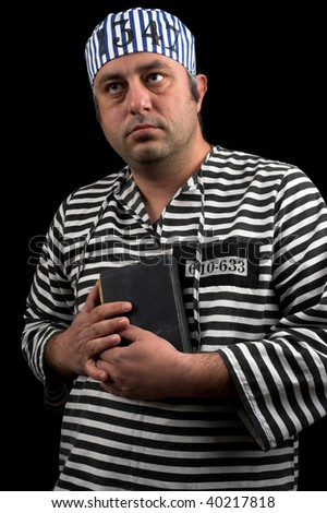 portrait of prisoner with book over black