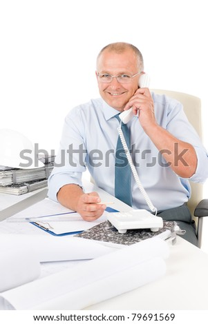 Portrait of professional architect with blueprints sitting behind table