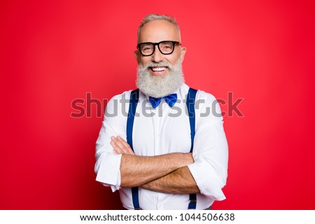Portrait of professional, cool, old man with beaming smile having his arms crossed, looking at camera, wearing blue bow-tie and suspenders, isolated on red background