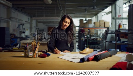 Portrait of professional fashion designer drawing a new shoe model according to the Italian tradition. Concept: fashion, design, mode, style