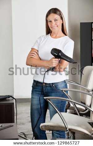 Portrait of professional female hairdresser holding hair dryer at salon