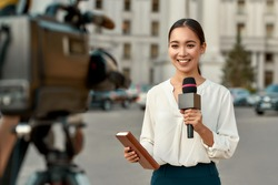 Portrait of professional female reporter at work. Young asian woman standing on the street with a microphone in hand and smiling at camera. Horizontal shot. Selective focus on woman