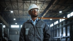 Portrait of Professional Heavy Industry Engineer Worker Wearing Uniform, Glasses, Hard Hat in Steel Factory. Smiling African American Industrial Specialist Standing in Metal Construction Manufacture.