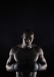 Portrait of professional male boxer against black background. Strong and muscular young man in boxing gear.
