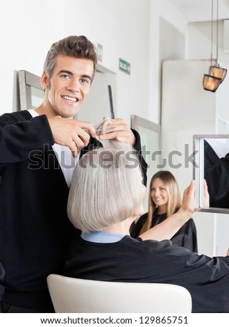 Portrait of professional male hairdresser cutting female client's hair at salon