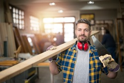 Portrait of professional middle aged carpenter with wood plank, handsaw and tools standing in his woodworking workshop while workers working in background.
