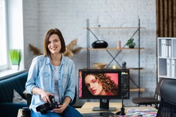 Portrait of professional photographer holding camera in photo studio. Workplace in office with camera, laptop, monitor, graphic drawing tablet and color palette. Retouching images. Creative agency.