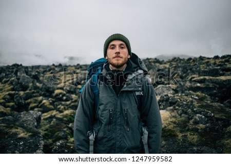 Portrait of proud and brave young adventurer hiker, explorer handsome man with trekking backpack stand on rocky hiking trail or path, look into camera. Outdoor vibes and adventures wanderlust #1247959582