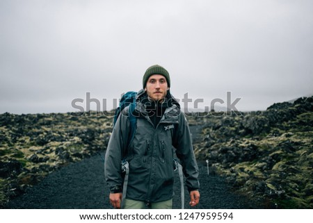 Portrait of proud and brave young adventurer hiker, explorer handsome man with trekking backpack stand on rocky hiking trail or path, look into camera. Outdoor vibes and adventures wanderlust #1247959594