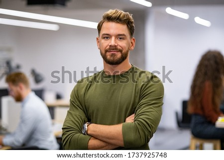 Portrait of proud businessman standing in creative office and looking at camera. Successful mid man entrepreneur standing with staff working in background. Satisfied young business man in agency.