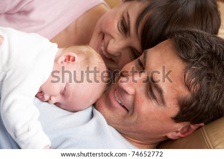 Portrait Of Proud Parents With Newborn Baby At Home