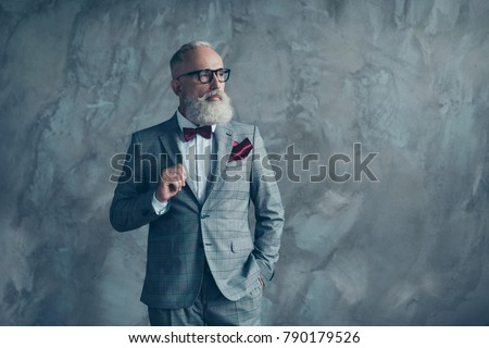 Portrait of proud respected confident handsome masculine virile vintage grey-haired sharp dressed in bespoke checkered grey suit with vinous handkerchief brutal macho isolated on concrete background