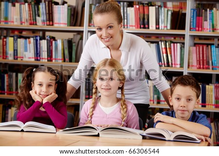 Portrait of pupils and teacher looking at camera with smiles in library