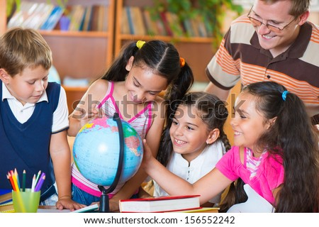 Portrait of pupils looking at globe with their teacher during geography lesson