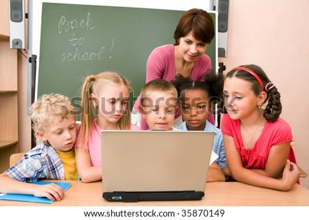 Portrait of pupils looking at the laptop display with teacher near by
