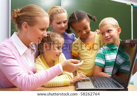 Portrait of pupils looking at the laptop while listening to teacher explaining something