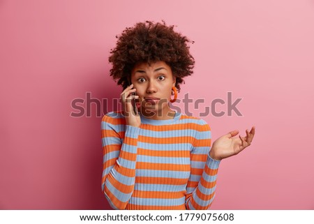 Portrait of questioned Afro American woman has telephone conversation and hesitates with answer, makes weighing gesture and raises palm doubtfully, being unaware and has no idea, not sure about Stockfoto ©