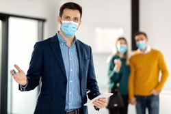 Portrait of real estate agent holding digital tablet and wearing face mask due to COVID-19 pandemic. There is a couple in the background.