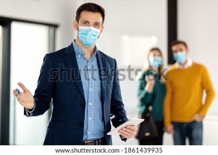 Portrait of real estate agent holding digital tablet and wearing face mask due to COVID-19 pandemic. There is a couple in the background.  ストックフォト ©