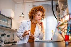 Portrait of red haired female scientist  sitting at desk and working with laptop during scientific experiment. Busy researcher typing scientific article. Female scientist working on laptop