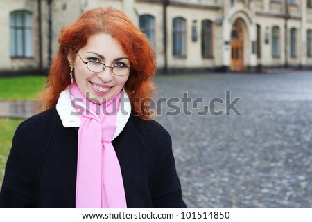 Portrait of red haired girl in front of the university