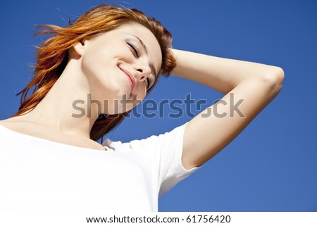 Portrait of red-haired girl in white on blue sky background.