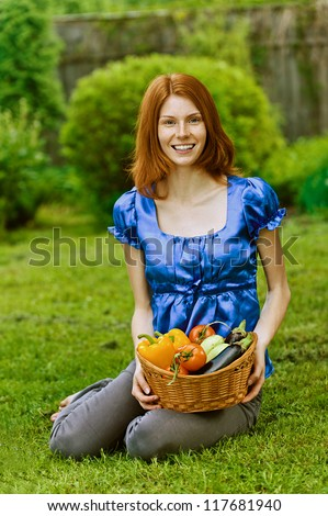 Portrait of red-haired smiling beautiful young woman in blue blouse with baskets of fruit and vegetables, against green of summer park.