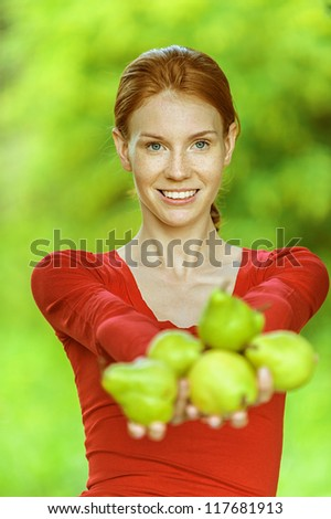 Portrait of red-haired smiling beautiful young woman in red blouse with pears, against green of summer park.