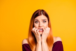 Portrait of red straight-haired attractive cute nice scared worried young girl, biting nails. Isolated over bright vivid yellow background