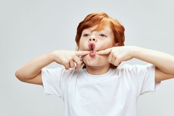 portrait of redhead child holding hands on cheeks with open mouth studio