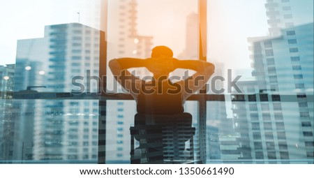 Portrait of relaxed businessman in modern office.Business young man relax after work of office window with business district view. #1350661490