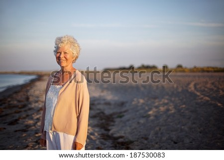 Portrait of relaxed elderly woman standing at the beach. Happy old lady standing alone on the beach with lots of copyspace. Relaxed senior caucasian woman outdoors smiling at camera