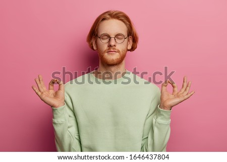 Portrait of relaxed ginger male tries to relax after hard work, meditates indoor, keeps hands in zen gesture, closes eyes, wears casual clothes, isolated over rosy wall. People, relaxation, yoga