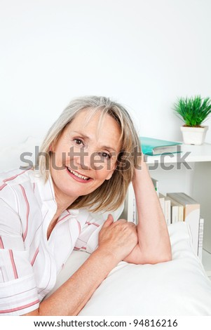 Portrait of relaxed senior woman smiling on couch at home