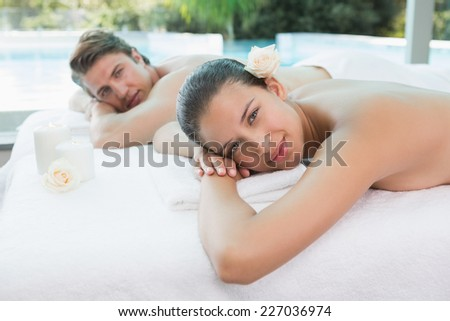 Portrait of relaxed young couple lying on massage table at spa center #227036974