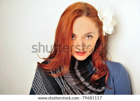 Portrait of relaxed young lady looking at the camera while leaning on wall
