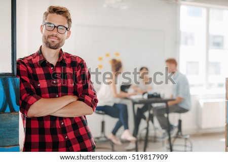 Portrait of relaxed young man standing in office with colleagues meeting in background.