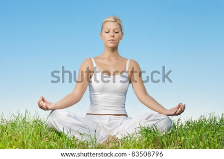 Portrait of relaxed young woman meditating outdoors.