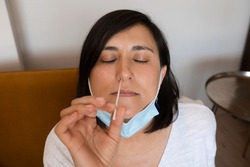 Portrait of relaxed young woman taking a Self-swabbing home tests for COVID-19 at home with Antigen kit. Introducing nasal stick to check the infection of Coronavirus. Quarantine, pandemic.
